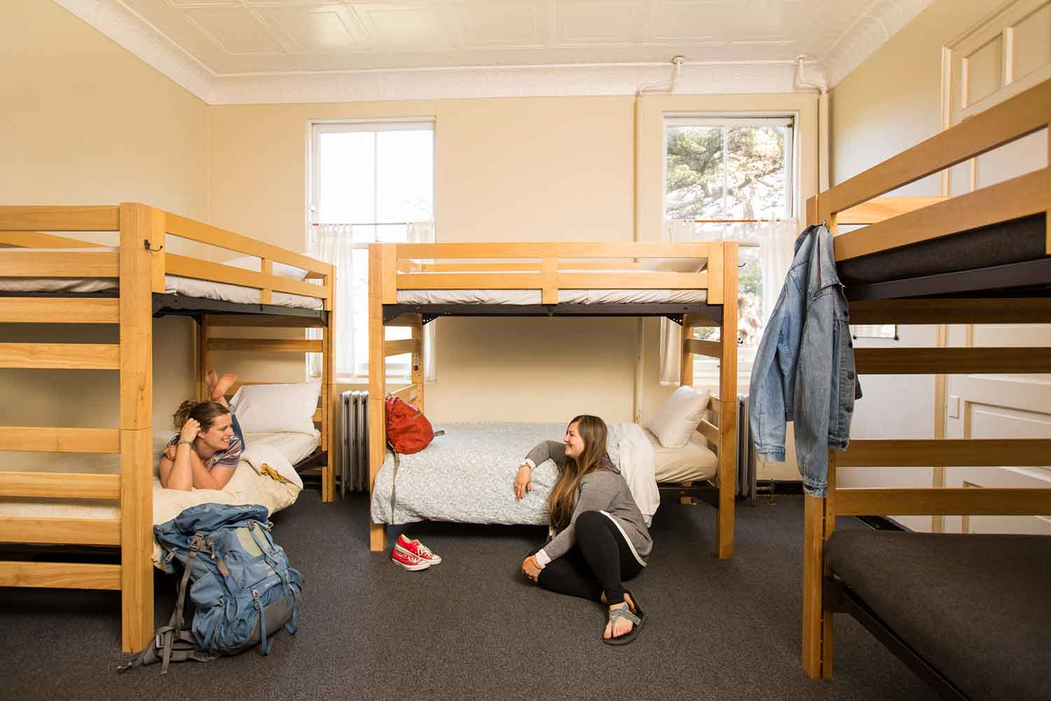 Room view with two young women talking in room with bunk beds.