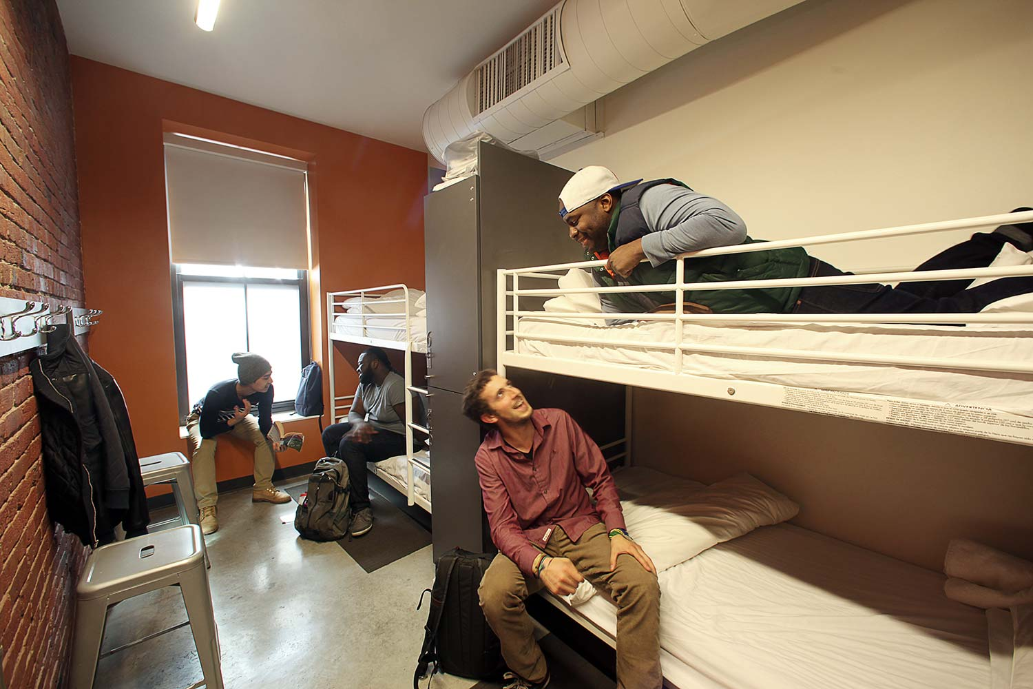 People sitting and talking in dorm room with 4 beds.