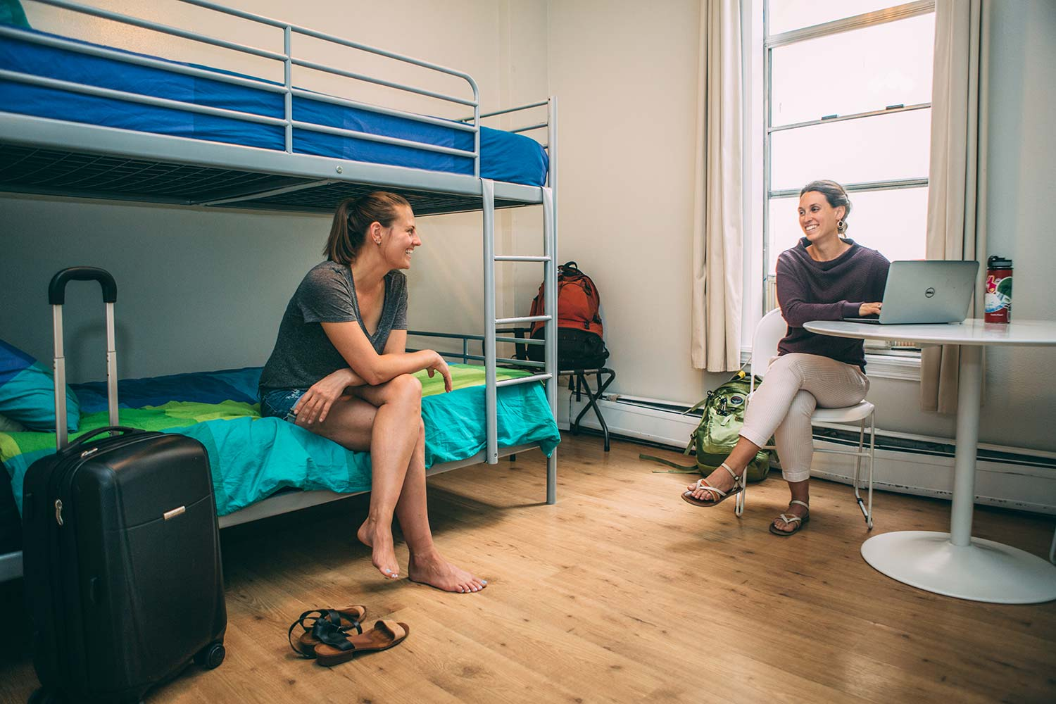 Two women talking in a room with two bunk beds.