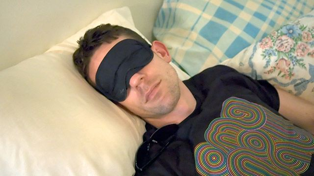 A man sleeping with an eye mask on