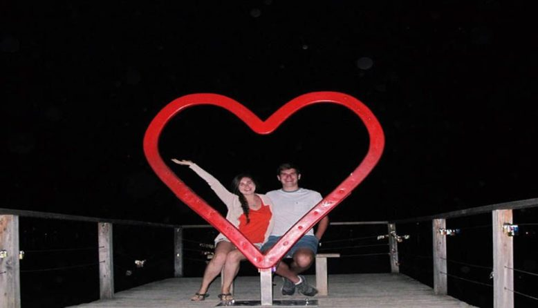 a couple posing with a heart sculpture
