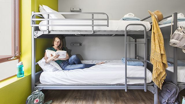 a woman reading a book on her dorm bed in a hostel