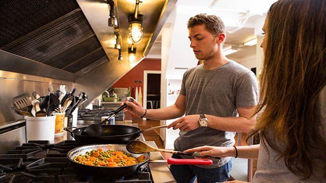 two hostel travelers making food