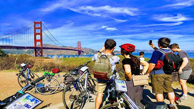 cyclists looking at the golden gate bridge