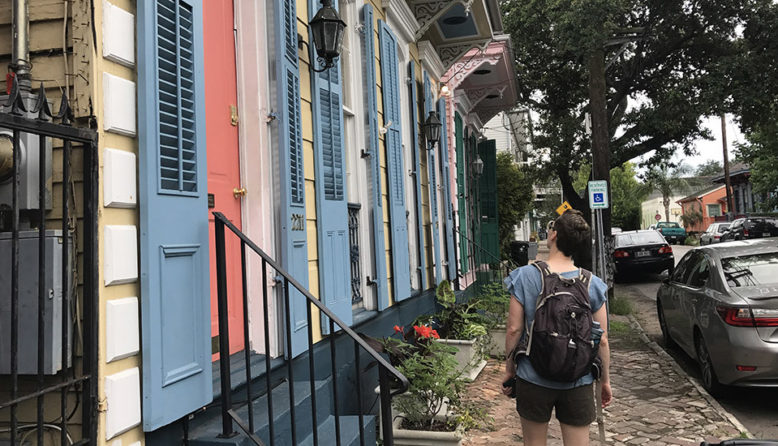 Woman in front of a row of colorful houses