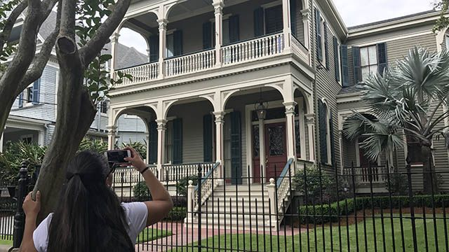 Woman taking picture of house in Garden District New Orleans