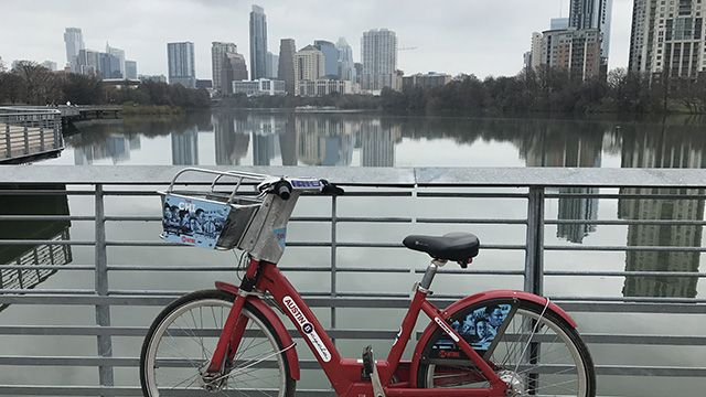 a bicycle in front of the Austin skyline