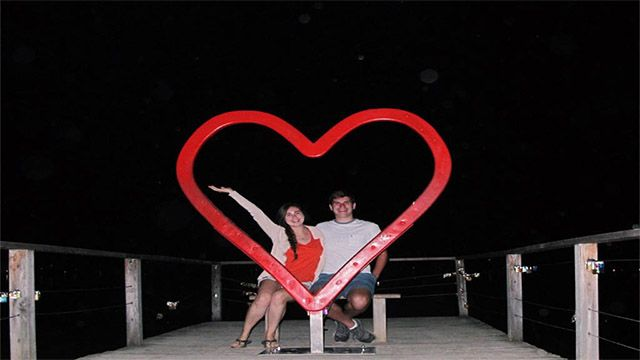 A couple posing with a heart art sculpture