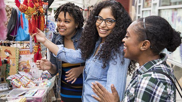 three women shopping at a street fair