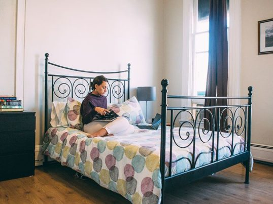 woman sitting on a bed in a private room at a hostel