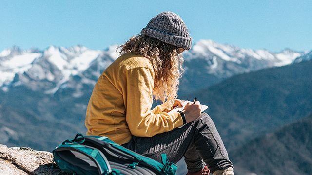 woman writing in a journal on top of a mountain
