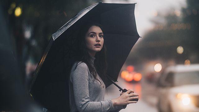woman standing under an umbrella