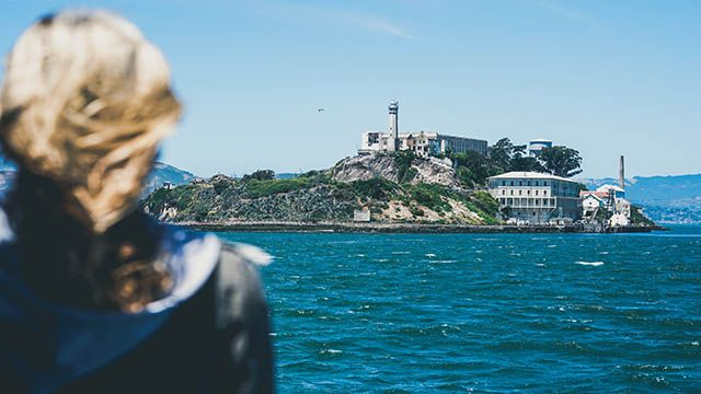 a woman looking at alcatraz island from the ferry