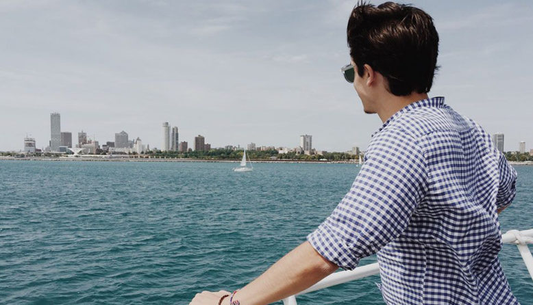 man looking over the railing of a ferry at the Milwaukee skyline