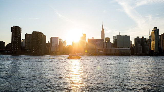 a view of Manhattan from the East River at sunset