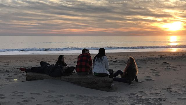 a group of travelers at Limantour Beach at sunset