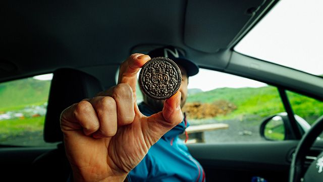 a man holding a cookie on a road trip