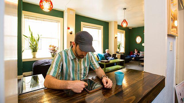 man using an ipad at HI San Francisco Downtown hostel