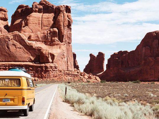 a van drives through arches national park