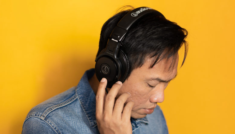 man with headphones against a yellow background