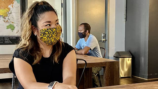 hostel guests wearing masks in a hostel lounge