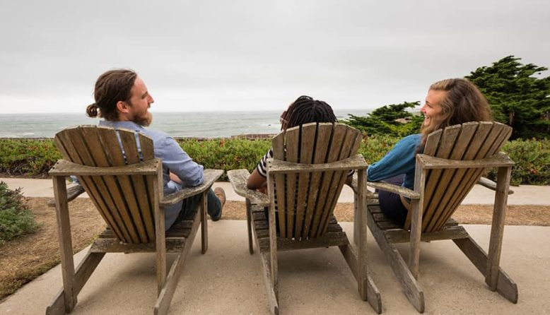 travelers relaxing in adirondack chairs at HI Pigeon Point Lighthouse