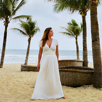 writer lola mendez in a white dress on the beach