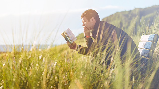 a man reading a book outside