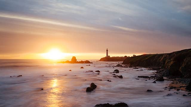 the sun setting behind pigeon point light house