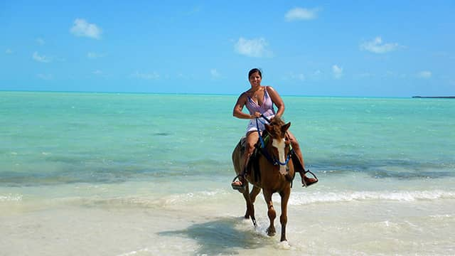 the author Jessica van Dop DeJesus on horseback in the water in Turks and Caicos