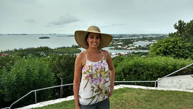 journalist Tinabeth Pina wearing a wide-brimmed hat overlooking the water in Bermuda