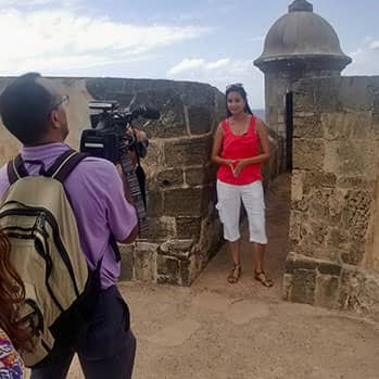 journalist Tinabeth Pina being filmed by a camera operator in Puerto Rico