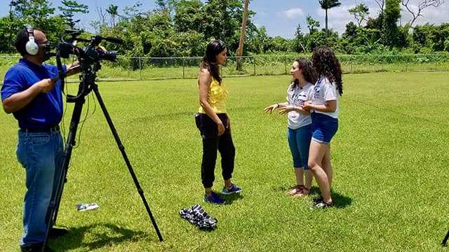 journalist Tinabeth Pina speaks with students while being filmed in Puerto Rico