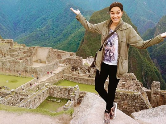 the author Tinabeth Pina in Peru overlooking ruins in the mountains