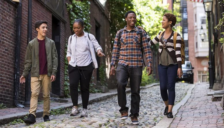a group of young people walks down a narrow street in Boston's Beacon Hill neighborhood