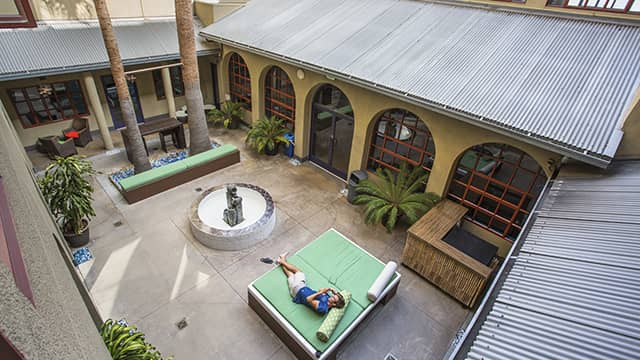 a man lies on an outdoor couch in the sun in HI Los Angeles Santa Monica's courtyard