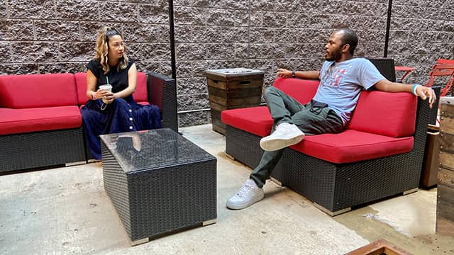 two people sit talking at a distance in the outdoor courtyard at a HI USA hostel