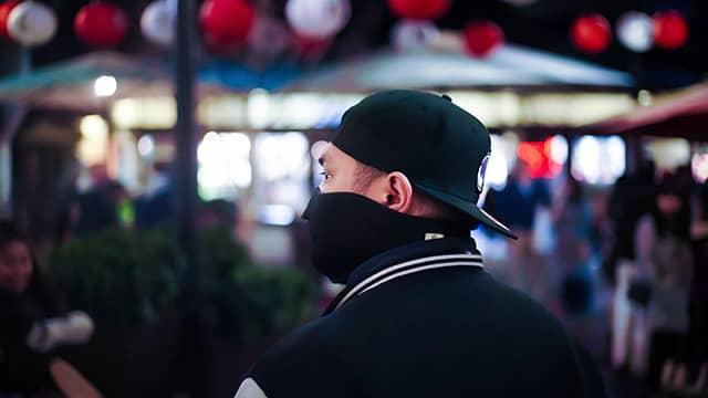 man in a mask walking through Little Tokyo in Los Angeles