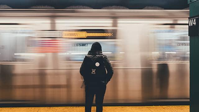 a New York City subway train passes as a woman waits on the platform