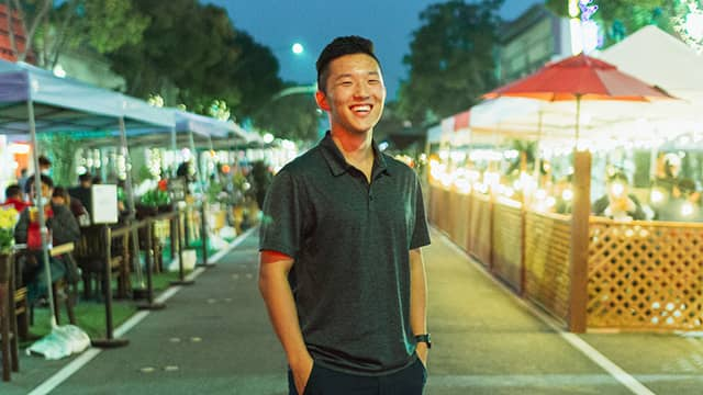 a man stands in the middle of a street full of outdoor dining parklets