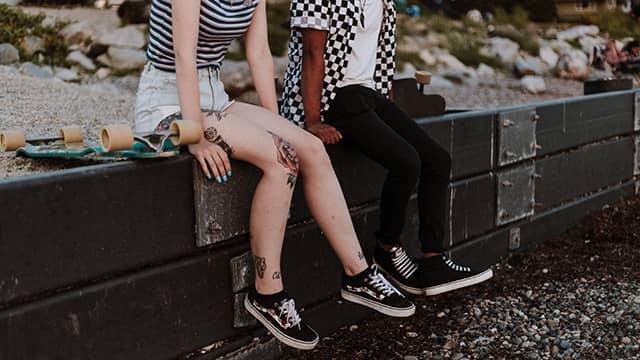 two skateboarders sit on a wall talking